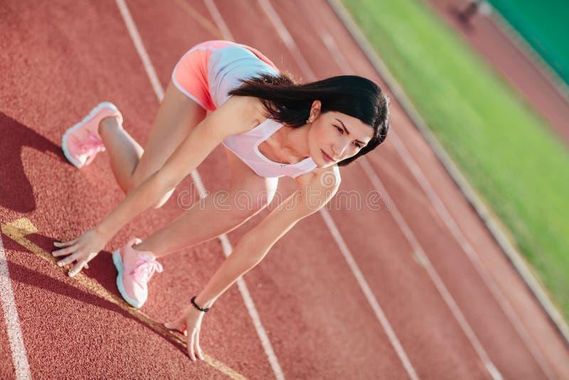 Ståenden av den unga sportiga kvinnan i rosa kortslutningar och ärmlösa tröjor är klara att köra och ställningar på start på stad arkivfoton