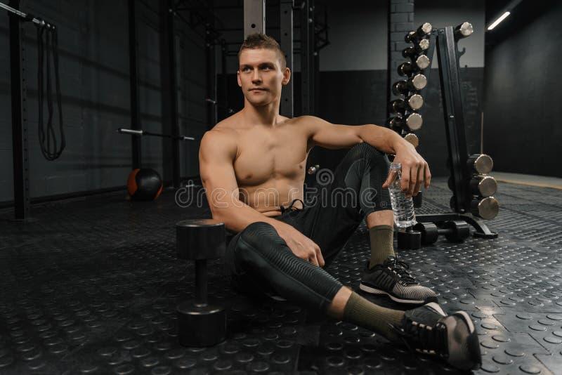Ståenden av den unga sportiga mannen med flaskan vilar i idrottshall efter genomkörare royaltyfria foton