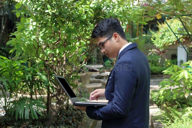 Ståenden av den unga stiliga affärsmannen använder en bärbar dator på hans händer i suddig bakgrund för natur royaltyfri bild