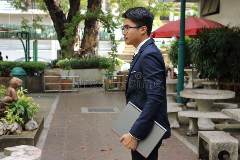 Ståenden av den unga stiliga affärsmannen rymmer en bärbar dator på hans händer i suddig bakgrund för natur arkivbild