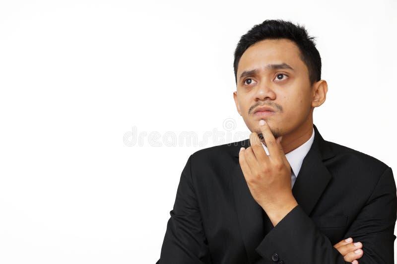 Ståenden av den unga tänkande mannen ser upp med den near framsidan för handen royaltyfria bilder