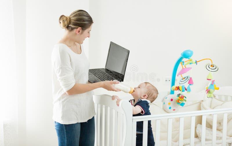 Ståenden av den unga upptagna kvinnan som arbetar på bärbara datorn och ger sig, mjölkar till henne behandla som ett barn sonen arkivbilder