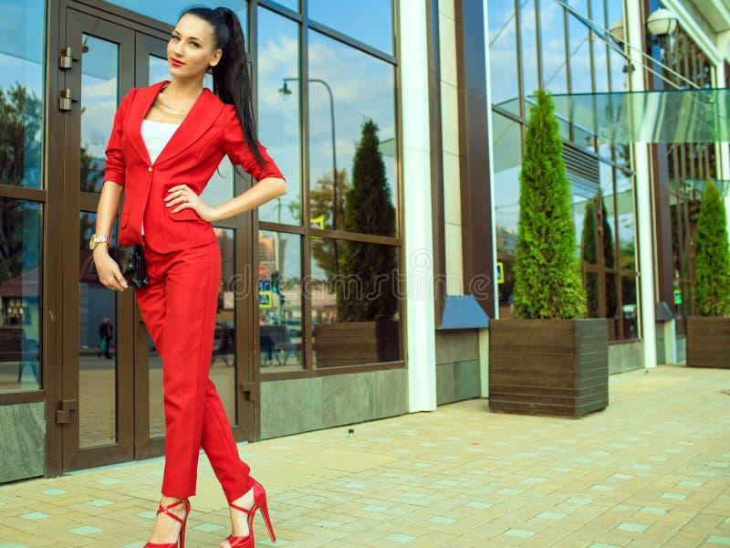 Ståenden av den unga ursnygga damen med den höga ponnysvansen i röd dräkt och hög-heeled skor av spegelförsett shoppar framme fön royaltyfria bilder