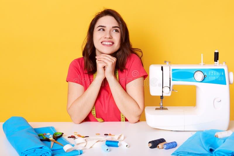 Ståenden av den yrkesmässiga positiva unga kvinnliga skräddaren som arbetar på symaskinen, bär den tillfälliga röda t-skjortan, h royaltyfria bilder