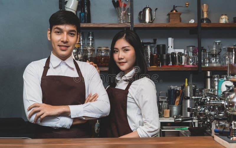 Ståenden av det asiatiska anseendet för parpartnerskapbaristaen med armar korsade att se kameran på räknarestången i kafét, servi royaltyfri bild