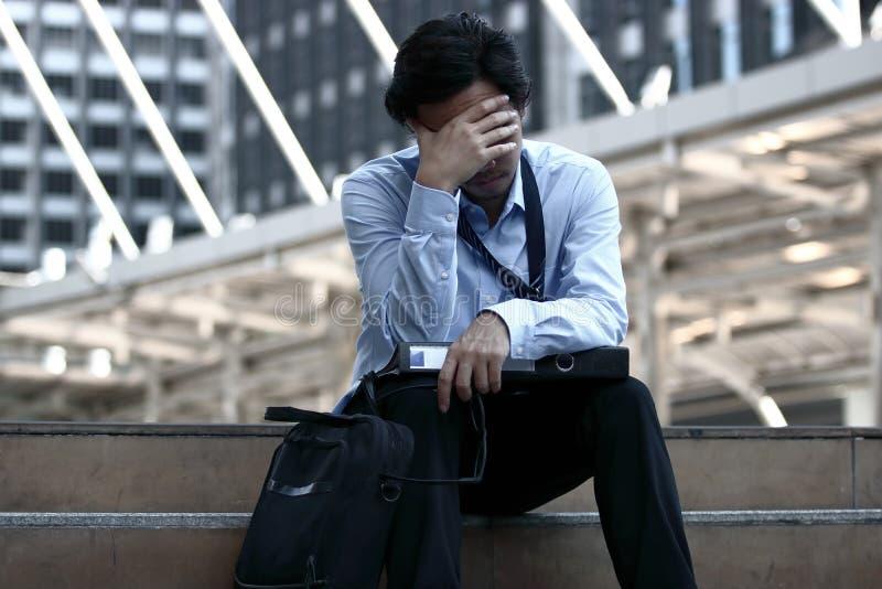 Ståenden av det frustrerade stressade unga asiatiska rörande huvudet för affärsmannen och stänger hans ögon han känner belastning royaltyfria foton