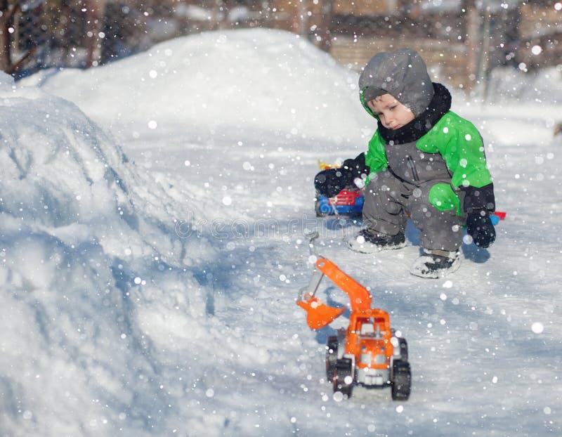 Ståenden av det gulliga lilla lilla barnet som sitter på snö och spelar med hans gula traktorleksak i, parkerar barn som leker ut royaltyfri fotografi