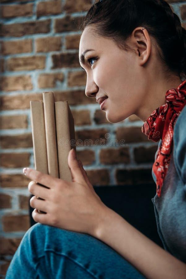 Ståenden av det härliga unga asiatiska kvinnainnehavet bokar och se bort arkivbild