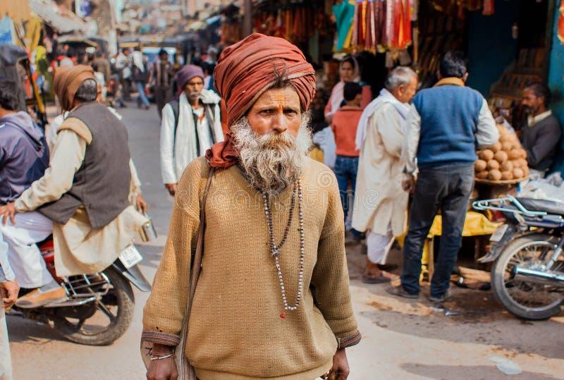 Ståenden av en äldre indisk man som går på marknadsgatan med diversehandel och, shoppar av asiatisk stad royaltyfria foton