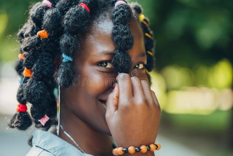 Ståenden av en afrikansk skönhet som ler den unga svarta kvinnan i, parkerar med solljussignalljuset och kopieringsutrymme royaltyfri foto