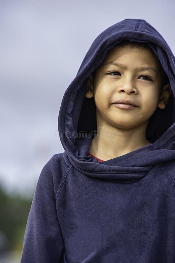 Ståenden av en asia pojke som bär ett vinteromslag, log lyckligt arkivfoton