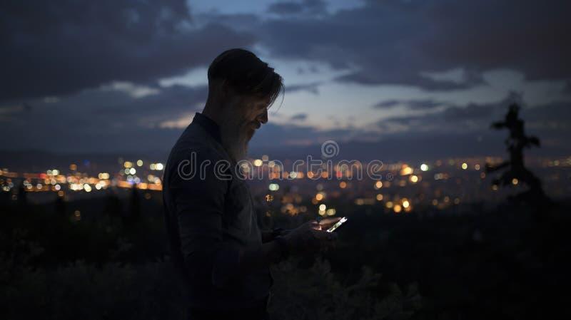 Ståenden av en attraktiv skäggig man, som är på ett berg som är högt över staden, tänder att skriva sms royaltyfri fotografi