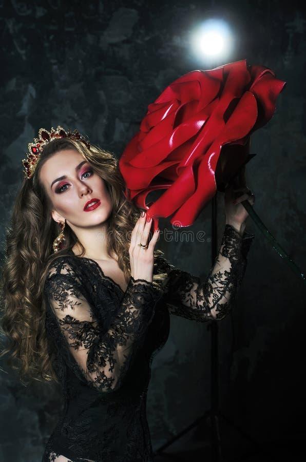 Ståenden av en attraktiv ung kvinna i en lång svart klänning med ett mycket stort steg på en grungeväggbakgrund royaltyfri foto