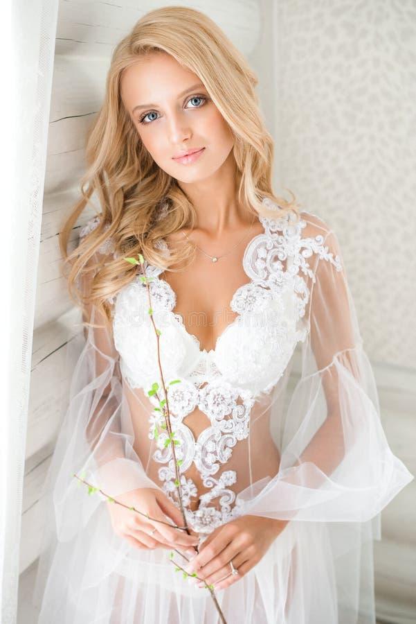 Ståenden av en bedöva blond brud snör åt in underkläderna arkivbilder