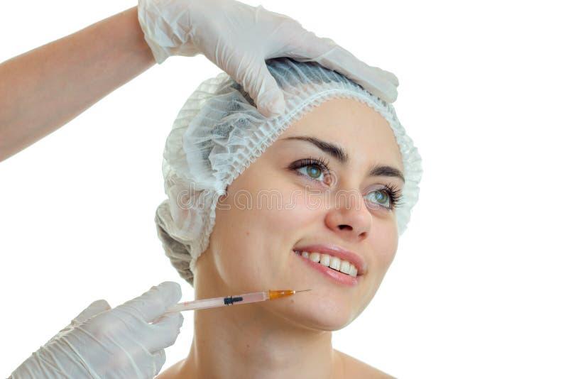 Ståenden av en charmig ung flicka i ett specialt lock för hår, som doktorn sätter in injektionen, och henne ler tätt arkivfoton