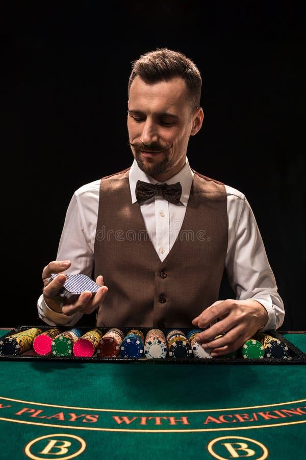 Ståenden av en croupier rymmer att spela kort som spelar gå i flisor på tabellen Svart bakgrund royaltyfri bild