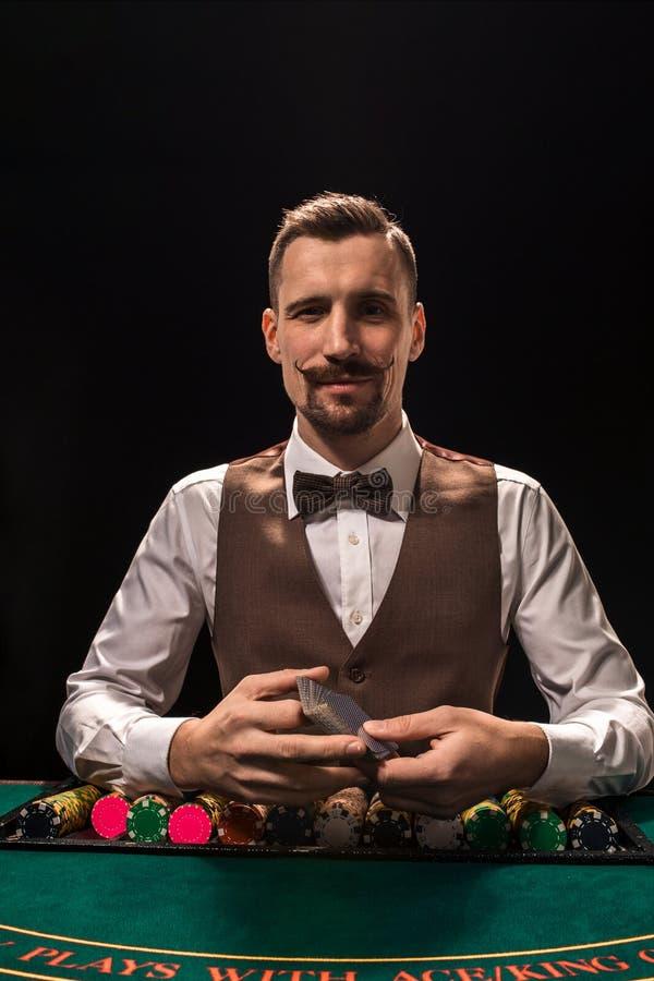 Ståenden av en croupier rymmer att spela kort som spelar gå i flisor på tabellen Svart bakgrund arkivfoto
