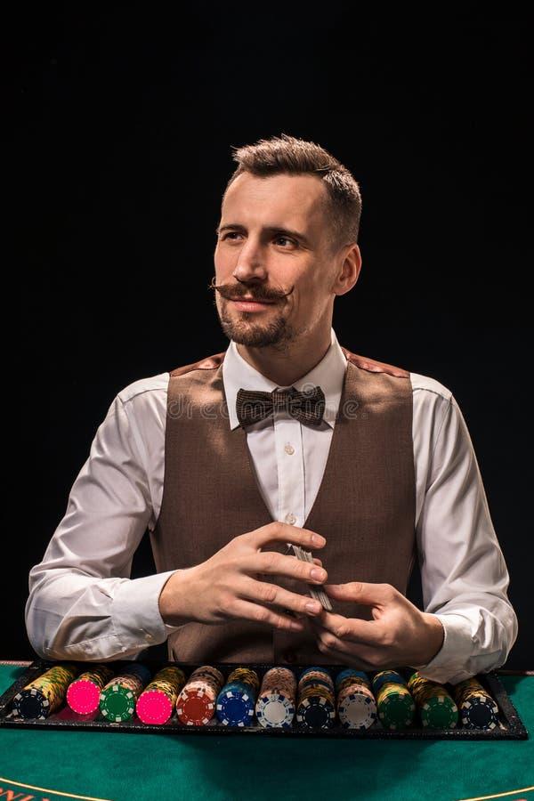 Ståenden av en croupier rymmer att spela kort som spelar gå i flisor på tabellen Svart bakgrund royaltyfria foton