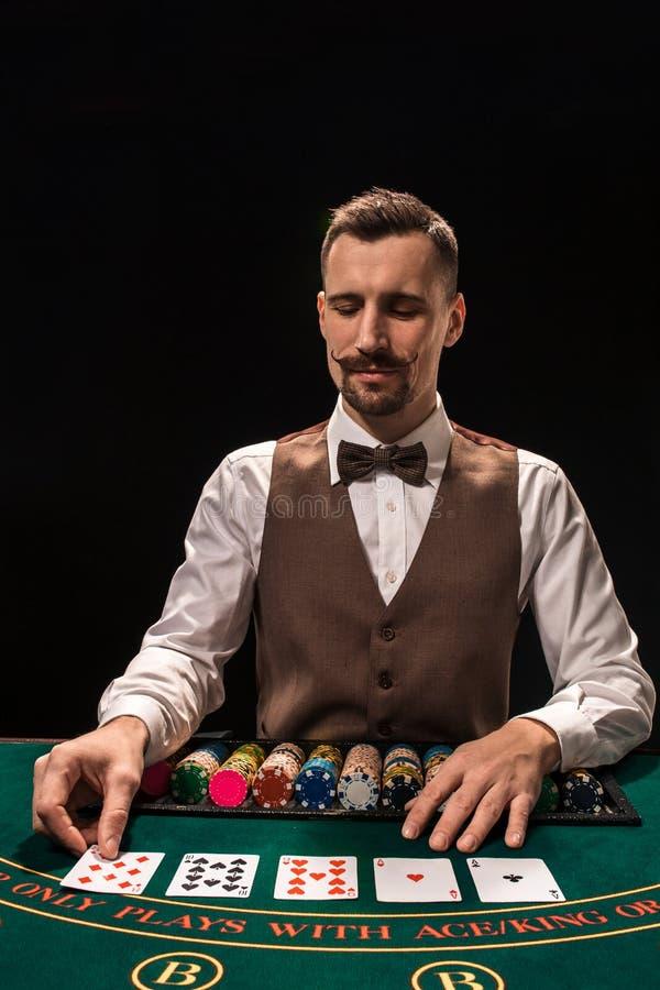 Ståenden av en croupier rymmer att spela kort som spelar gå i flisor på tabellen Svart bakgrund arkivfoton