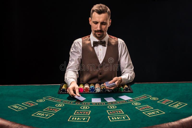 Ståenden av en croupier rymmer att spela kort som spelar gå i flisor på tabellen Svart bakgrund arkivbild