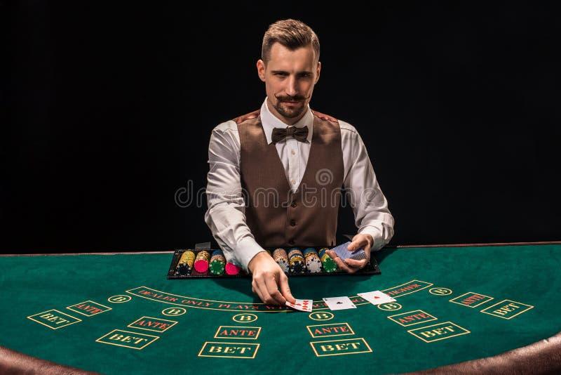 Ståenden av en croupier rymmer att spela kort som spelar gå i flisor på tabellen Svart bakgrund arkivbilder