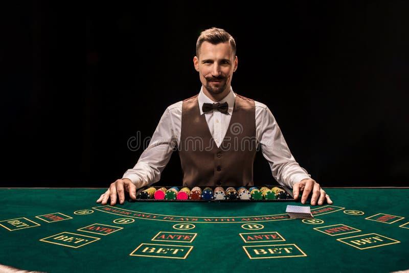 Ståenden av en croupier rymmer att spela kort som spelar gå i flisor på tabellen Svart bakgrund royaltyfri foto