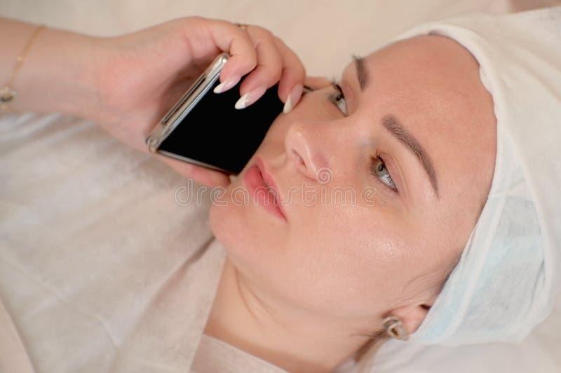 Ståenden av en flicka i en handduk ligger på soffan och samtal på en smartphone Den unga kvinnan kopplar av i brunnsorten royaltyfri fotografi