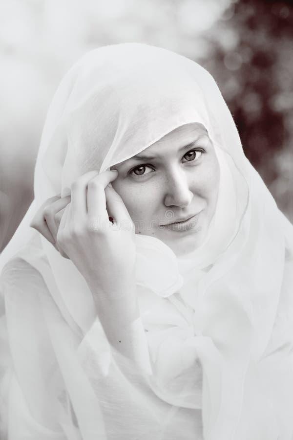 Ståenden av en flicka vested med en vit torkduk arkivbild