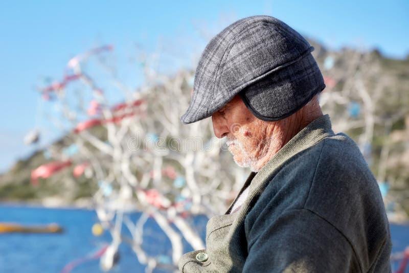 Ståenden av en gamal man bära ett lock på åldern av 60-tal som tar, ta sig en tupplur nära sjösidan på en solig dag royaltyfri foto