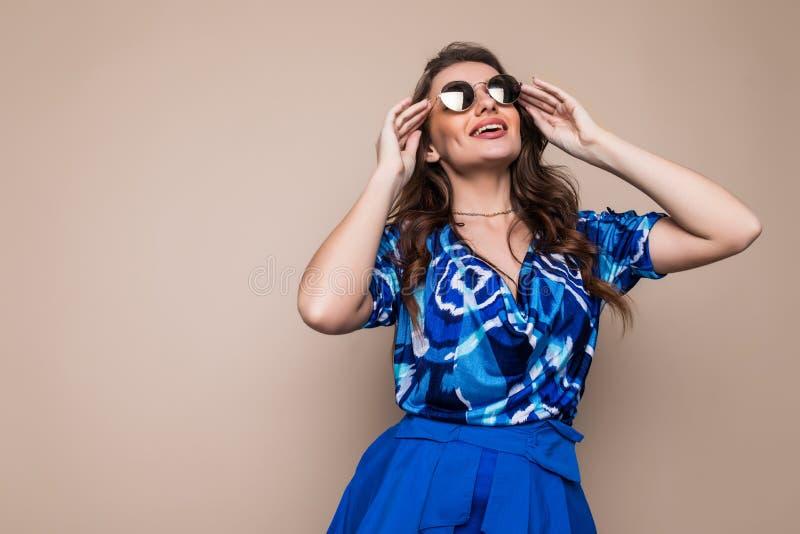 Ståenden av en glad iklädd blått för ung kvinna klär och solglasögon som ser kameran som isoleras över brun bakgrund arkivbilder