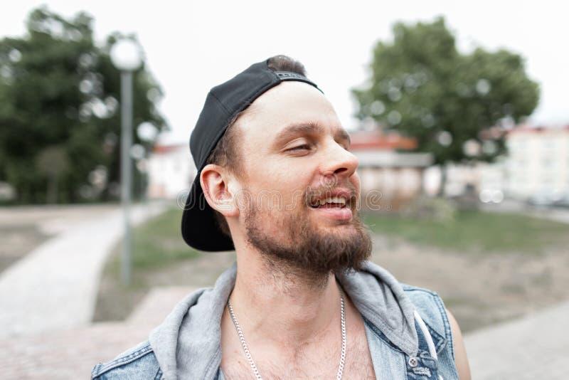 Ståenden av en gladlynt ung man med ett skägg som ler i ett stilfullt svart lock i en trendig blå grov bomullstvill, tilldelar st royaltyfria bilder
