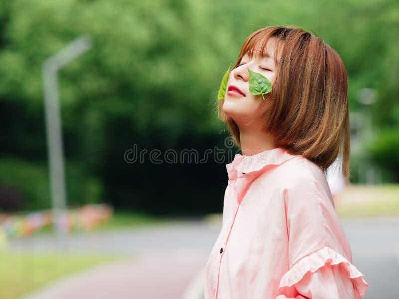Ståenden av en gullig kinesisk flicka i rosa klänningögon stängde sig med två gröna sidor på hennes framsida i sommarskog arkivbilder