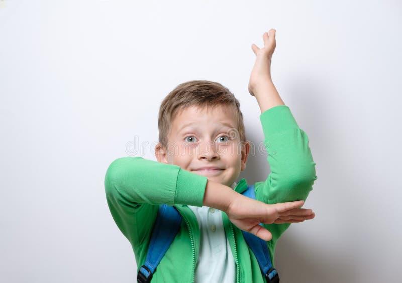 Ståenden av en gullig skolpojke med blått vandrar på lönelyft en hand fotografering för bildbyråer