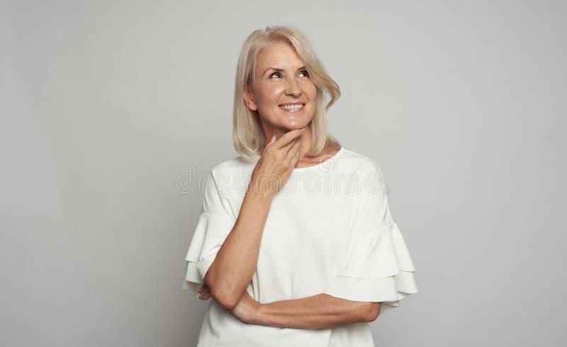 Ståenden av en härlig 50 år kvinna är att le som ser upp royaltyfria foton