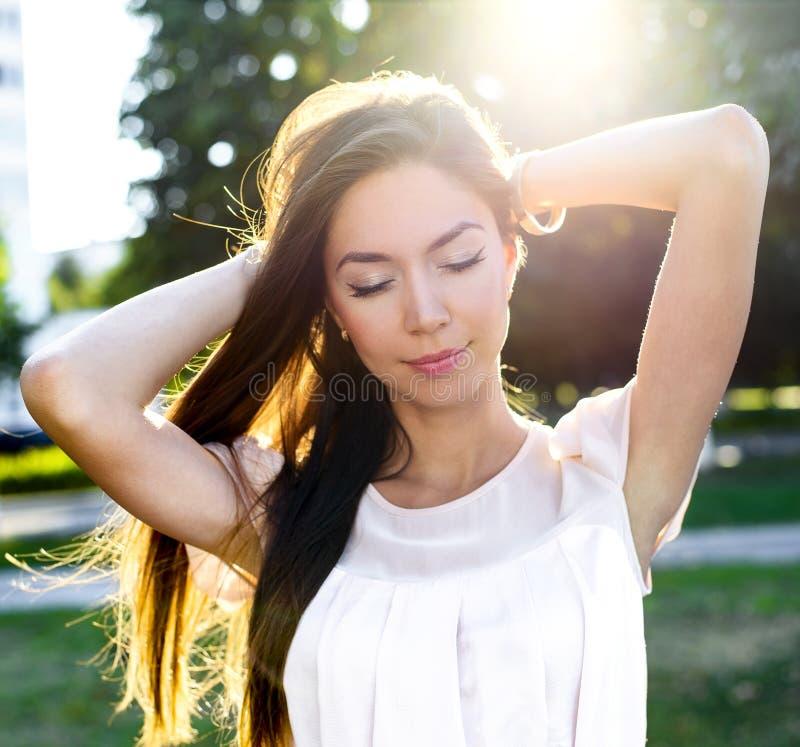 Ståenden av en härlig brunett parkerar in hållande hår tycker om din semester, i ljust solljus Stads- modestil royaltyfria foton