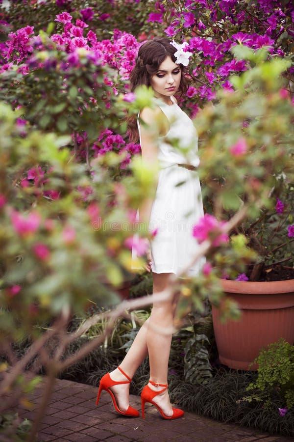 Ståenden av en härlig brunettkvinna i rosa färger klär och det färgrika sminket utomhus i azaleaträdgård royaltyfri fotografi