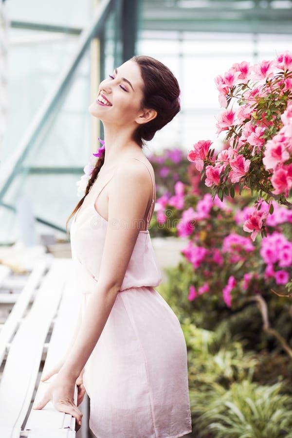 Ståenden av en härlig brunettkvinna i rosa färger klär och det färgrika sminket utomhus i azaleaträdgård royaltyfri bild