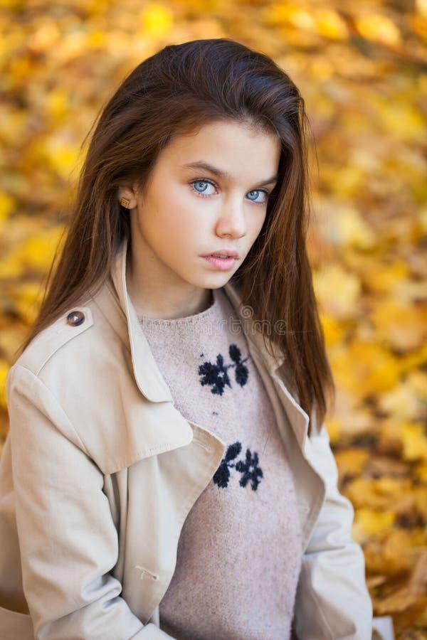 Ståenden av en härlig brunettliten flicka, höst parkerar det fria arkivfoto