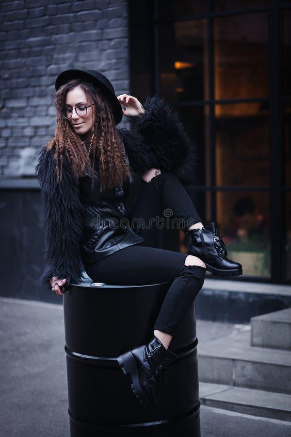 Ståenden av en härlig flicka med bruntögon i exponeringsglas i en svart hatt och lag med päls sitter på en trumma i arkivfoto