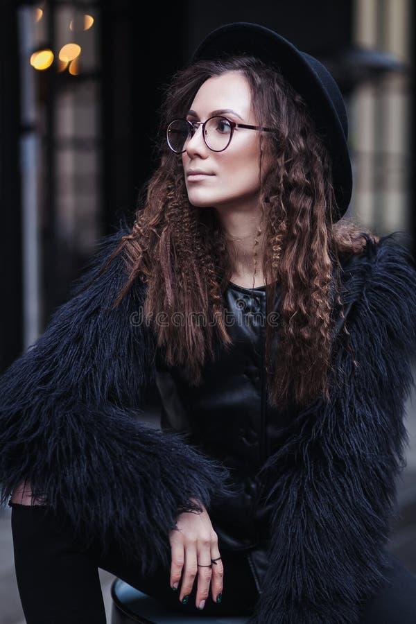 Ståenden av en härlig flicka med brunt synar i exponeringsglas i en svart hatt och ett lag med päls i cityscapen som bort ser arkivbilder
