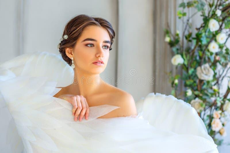 Ståenden av en härlig flicka som slås in i den vita ängeln, påskyndar royaltyfria foton