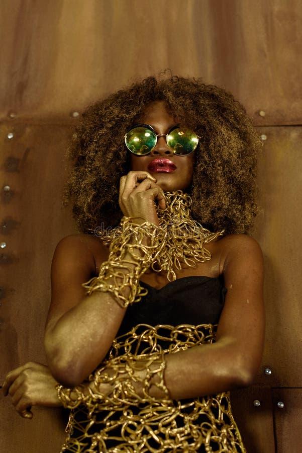 Ståenden av en härlig fundersam ung afrikansk kvinna som bär guld- smycken och solglasögon som rymmer handen nära, vänder mot, br royaltyfri bild