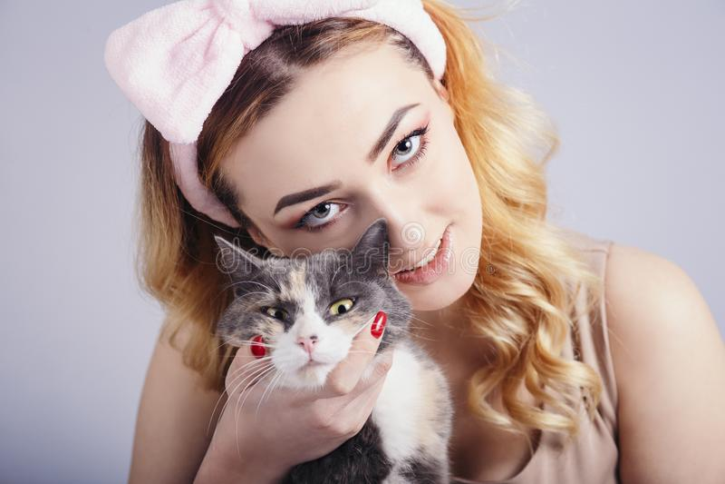 Ståenden av en härlig gullig flicka med en katt i händer, den unga kvinnan i en huvudbindel för utgör på en grå studiobakgrund me royaltyfria foton