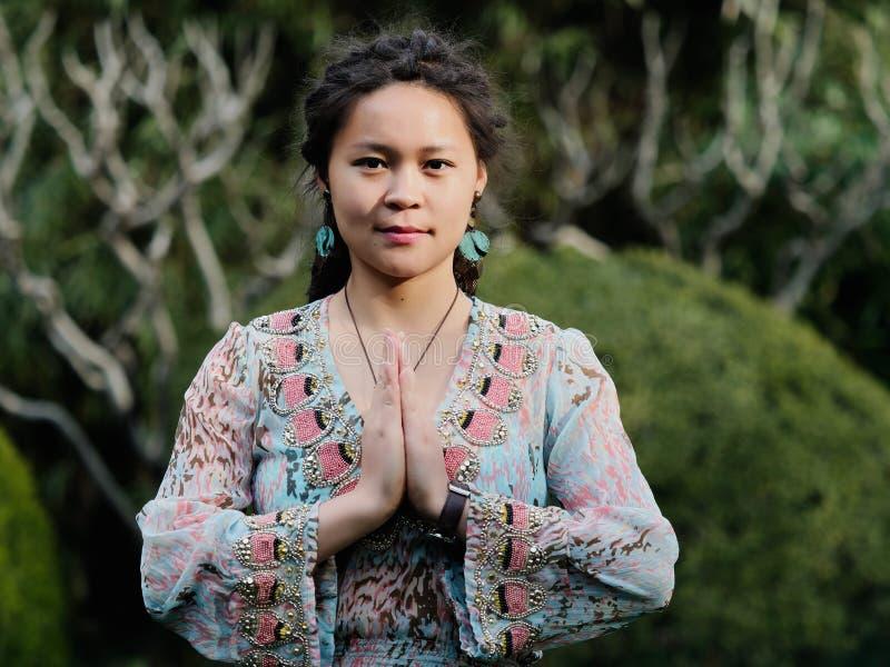 Ståenden av en härlig kinesisk flicka med gulliga dreadlocks gömma i handflatan tillsammans som bönens position i solig dag royaltyfri fotografi