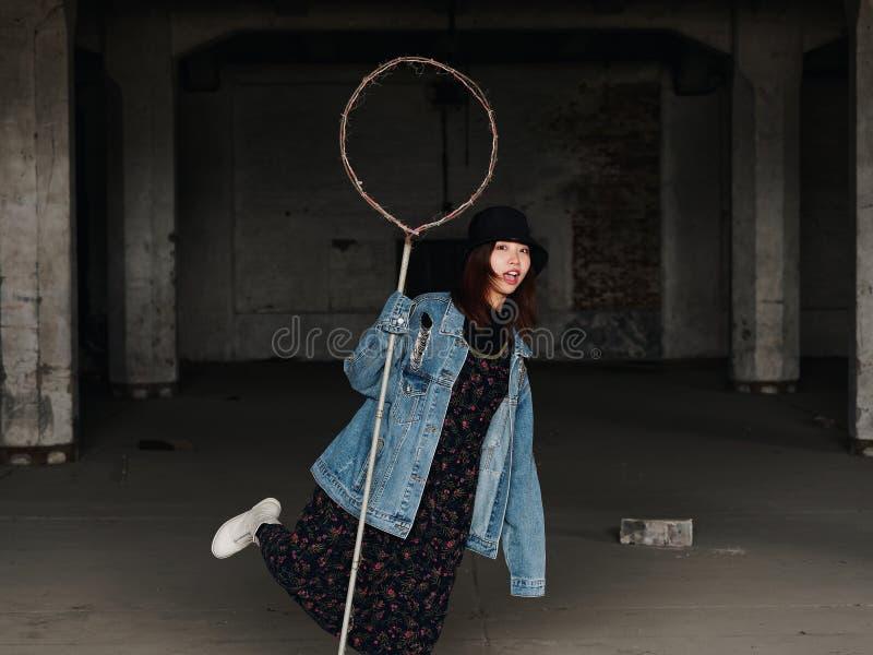 Ståenden av en härlig kinesisk kvinna i jeans och den svarta hatten rymmer en leksak som lasso och gör framsidor i en otvungenhet royaltyfri fotografi