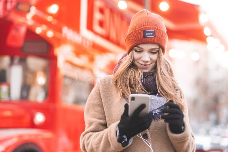 Ståenden av en härlig kvinna i hörlurar står på bakgrunden av en härlig bokeh, bruk en smartphone och leenden för stad fotografering för bildbyråer