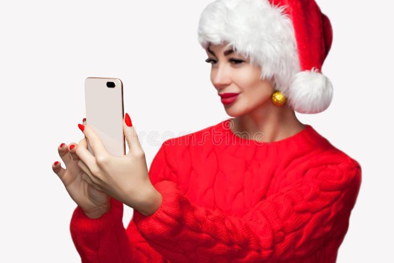 Ståenden av en härlig kvinna i en röd hatt och en tröja gör selfie på en mobiltelefon royaltyfria foton