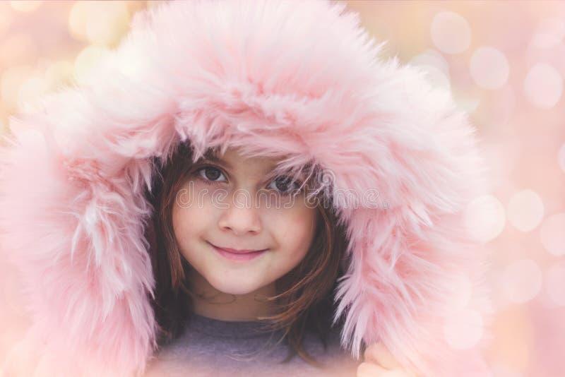 Ståenden av en härlig liten flicka med rosa färger pälsfodrar huven royaltyfri bild