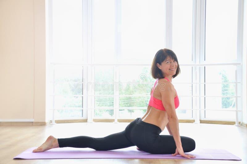 Ståenden av en härlig mogen kvinna som placerar i yoga, poserar på idrottshallen royaltyfri foto