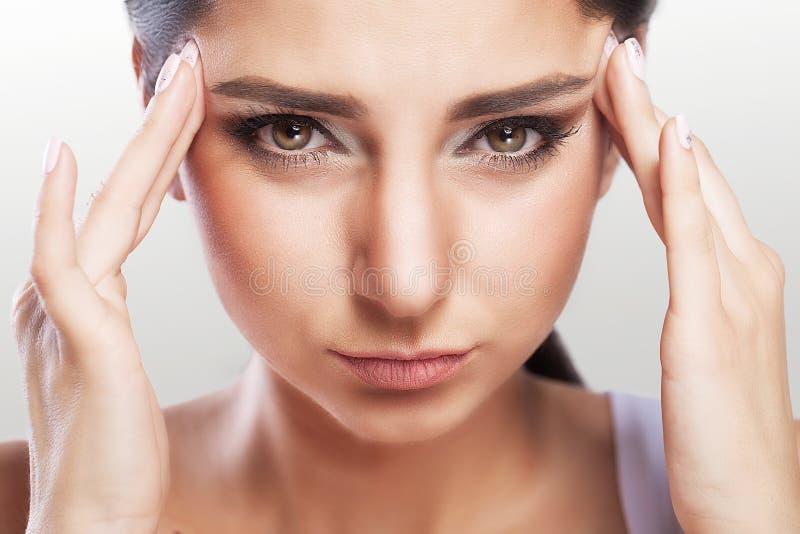 Ståenden av en härlig ung brunett med en kal skuldra, känner den stora huvudvärken, hälsoproblem, migrän, yrkesmässig makeup royaltyfria bilder